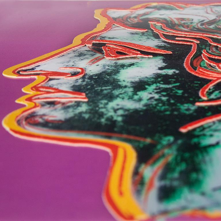 Η εικόνα εμφανίζει το αντίγραφο έργου τέχνης που δημιουργήθηκε με την πρακτική της ανάγλυφης εκτύπωσης πάνω σε επιφάνεια πλέξι γκλας. Το πρωτότυπο έργο ανήκει στον καλλιτέχνη Άντυ Γουόρχολ, με τίτλο Μέγας Αλέξανδρος. Η φωτογραφία παρουσιάζει το αντίγραφο και τις ανάγλυφες γραμμές της σύνθεσης σε έντονα χρώματα του κόκκινου, κίτρινου και πράσινου καθώς ένα γυναικείο χέρι διερευνά απτικά το αντίγραφο.