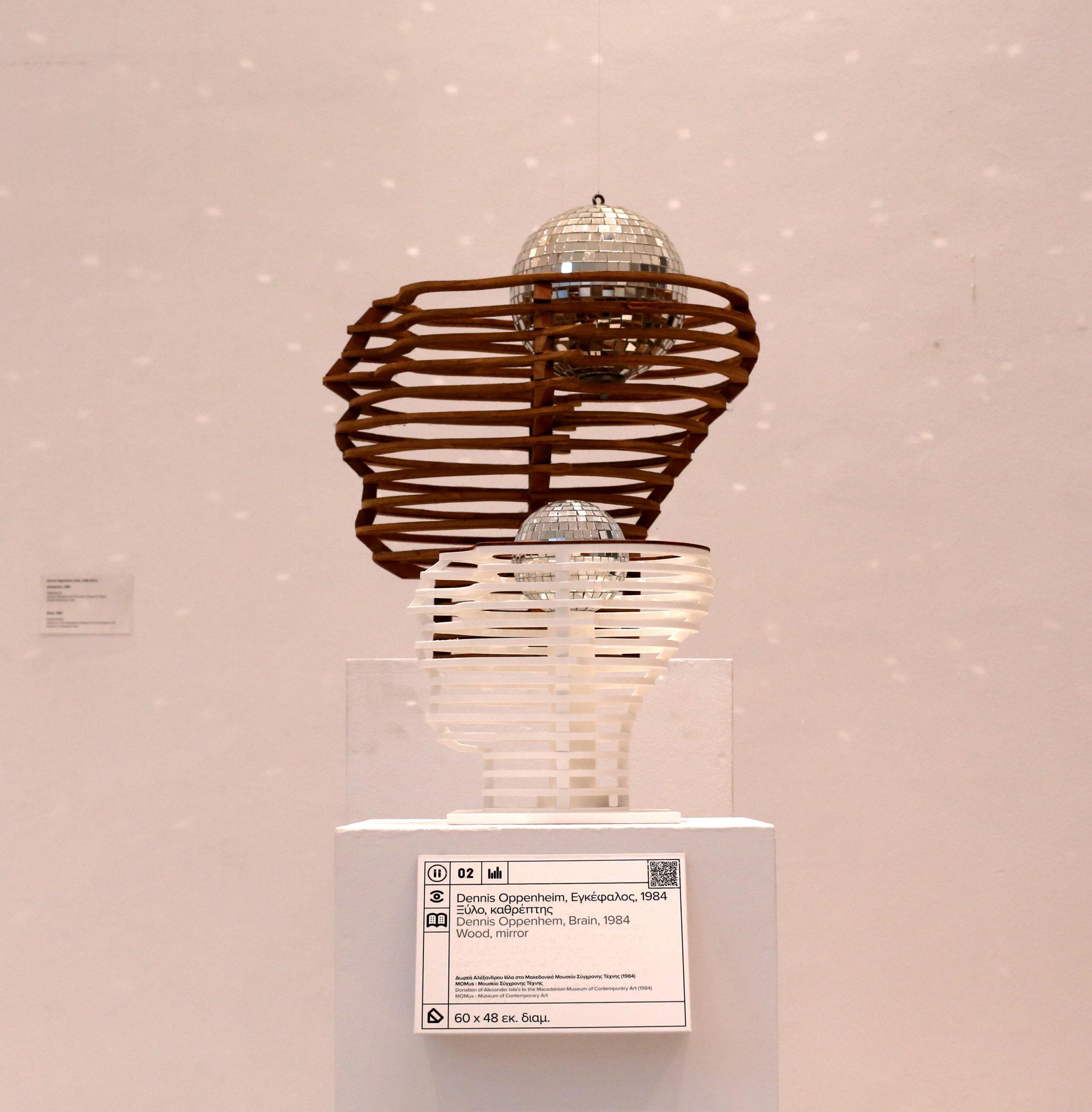 Το έργο Εγκέφαλος του Ντέννις Οππενχαημ και ακριβώς μπροστά του σε ένα βάθρο είναι τοποθετημένο το απτικό βοήθημα του έργου. Το απτικό βοήθημα είναι το ένα τρίτο του πρωτότυπου έργου σε μέγεθος και έχει δημιουργηθεί με την τεχνολογία της τρισδιάστατης εκτύπωσης σε λευκό πλαστικό. Στην ανώτερη φέτα του κεφαλιού έχει τοποθετηθεί μια φέτα ξύλου ώστε να παραπέμπει το υλικό του πρωτότυπου έργου. Επίσης, μια μπάλα από καθρέπτες έχει τοποθετηθεί στο κέντρο της κενής κεφαλής ώστε ο επισκέπτης να είναι σε θέση να ψηλαφίσει το σύνολο του έργου και να εξάγει τις δικές του εντυπώσεις από την επαφή του με το απτικό βοήθημα. Στην μπροστινή πλευρά του βάθρου υπάρχει λεζάντα που φέρει πληροφορίες σε μεγαλογράμματη γραφή και τη μεταγραφή τους σε ελληνική μπραιγ γραφή ενώ στην άνω δεξιά γωνία υπάρχει QR κωδικός ώστε οι επισκέπτες σκανάρωντας με τα κινητά τους τηλέφωνα να είναι σε θέση να ακούσουν την περιγραφή του έργου.
