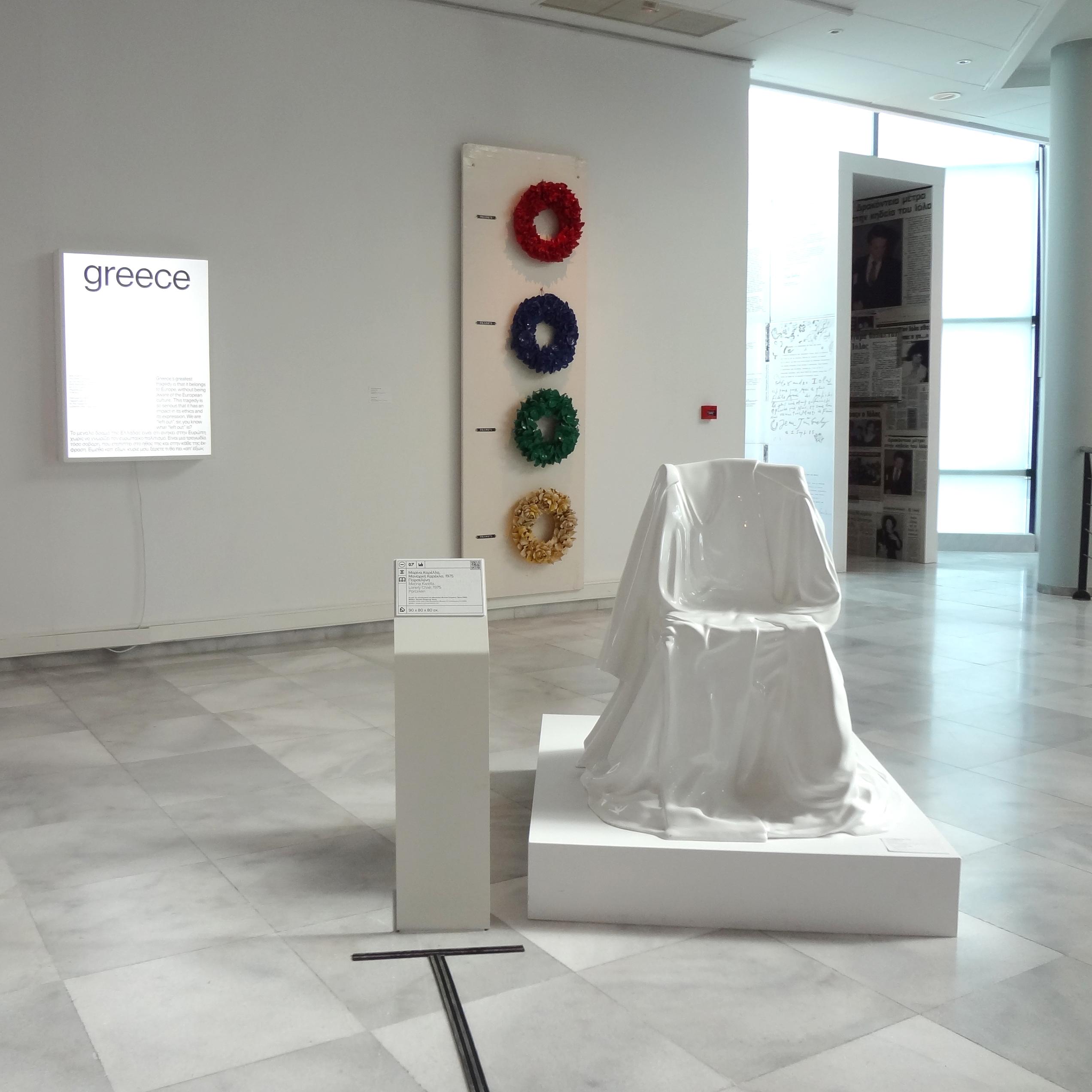 Το έργο τέχνης της Μαρίνας Καρέλλα. Αριστερά του έργου βρίσκεται ένα μεταλλικό σταντ που φέρει τη λεζάντα του έργου. Διακρίνεται ο οδηγός όδευσης στο πάτωμα που οδηγεί στη λεζάντα και το έργο. Στο βάθος διακρίνονται άλλα εργα της συλλογής του μουσείου.