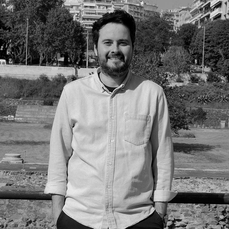 Στην εικόνα εμφανίζεται ο Δημήτρης Μουχταρόπουλος, ένας νέος άνδρας με κοντά μαύρα μαλλιά και κοντό μούσι. Φοράει ανοιχτόχρωμο πουκάμισο και κοιτάζει το θεατή χαμογελόντας ενώ έχει τα χέρια του κοντά στον κορμό μέσα στις τσέπες του παντελονιού του. Στο φόντο της εικόνας διακρίνεται η αρχαία ρωμαϊκή αγορά της Θεσσαλονίκης.