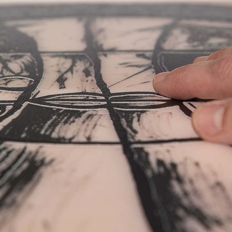 Η εικόνα εμφανίζει το αντίγραφο έργου τέχνης που δημιουργήθηκε με την πρακτική της ανάγλυφης εκτύπωσης πάνω σε επιφάνεια πλέξι γκλας. Το πρωτότυπο έργο ανήκει στον καλλιτέχνη Βίκτωρ Μπράουνερ, με τίτλο Σύνθεση. Η φωτογραφία παρουσιάζει το αντίγραφο και τις ανάγλυφες γραμμές της σύνθεσης σε χρώμα μαύρο καθώς ένα γυναικείο χέρι διερευνά απτικά το αντίγραφο.