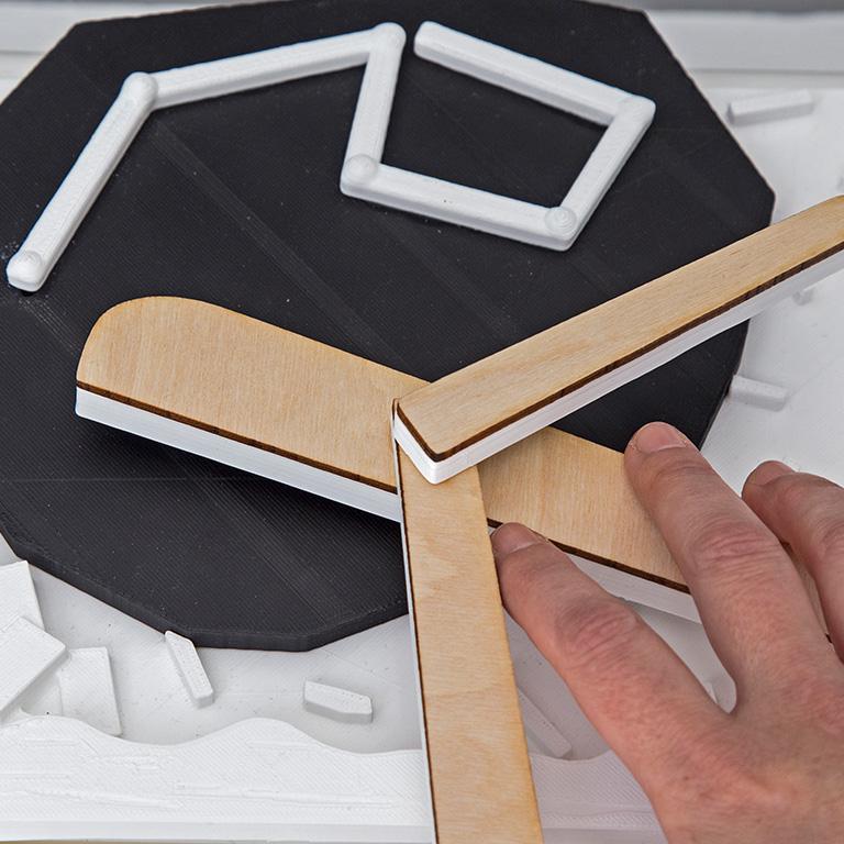 Η εικόνα εμφανίζει λεπτομέρεια από το αντίγραφο έργου τέχνης που δημιουργήθηκε με την πρακτική της τρισδιάστατης εκτύπωσης σε χρώμα λευκό και μαύρο. Το πρωτότυπο έργο ανήκει στον καλλιτέχνη Αλέξη Ακριθάκη, με τίτλο Αεροπλάνο. Η φωτογραφία παρουσιάζει το πιστό αντίγραφο σε μικρότερη κλίμακα και τις λεπτομέρειες της ανάγλυφης αναπαραγωγής καθώς ένα γυναικείο χέρι ψηλαφεί τα φτερά της αναπαραγωγής του αεροπλάνου.
