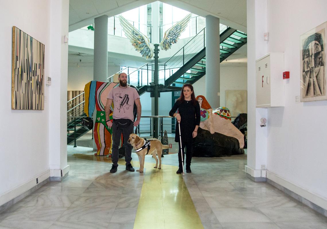 Φωτογραφία από το ισόγειο της Αίθουσας Αλέξανδρου Ιόλα του MOMus-Μουσείου Σύγχρονης Τέχνης στην οποία εμφανίζονται η Φανή Τσικούρα και ο Θανάσης Σιδέρης με τη Φρίντα-σκύλο οδηγό μέσα στη συλλογή έργων όπου εφαρμόζεται το πρόγραμμα Mind's Eye. Η Φανή και ο Θανάσης φαίνεται να κινούνται στο χώρο της συλλογής του μουσείου με φόντο τα έργα της συλλογής: Ψηλά διακρίνεται το έργο Φτερά του Παύλου Διονυσόπουλου, πίσω από τη Φανή και το Θανάση διακρίνουμε τμήμα από τα γλυπτά Αδάμ και Εύα της Νίκι ντε Σαντ Φάλ ενώ στο διάδρομο μπροστά από τους εικονιζόμενους στους πλαϊνούς τοίχους μπορούμε να διακρίνουμε το έργο Σύνθεση του Βίκτωρ Μπράουνερ και έργο του Ρομπέρτο Κρίπα.