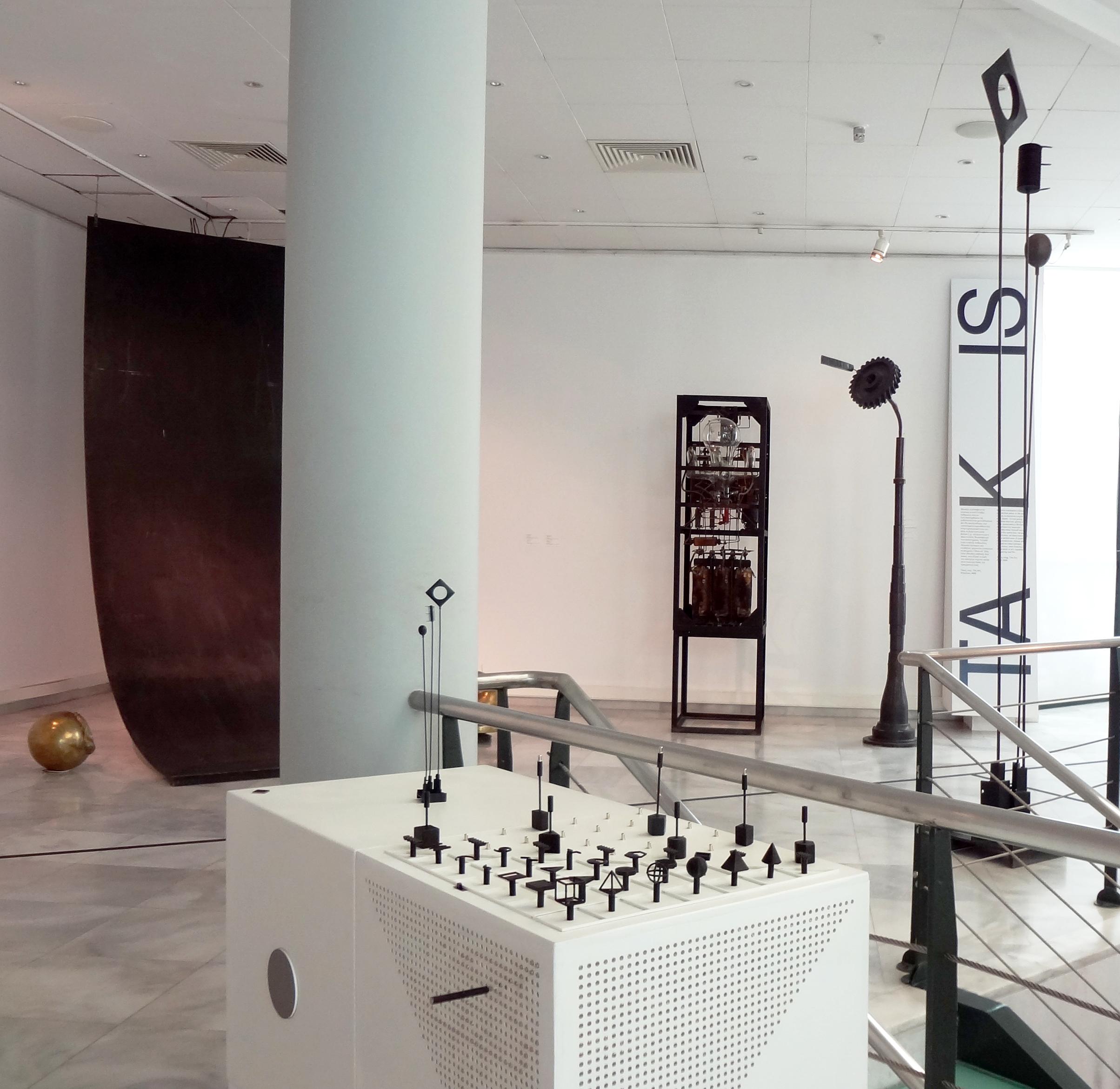 Διαδραστικά Μουσειοπαιδαγωγικά Αντικείμενα για την ερμηνεία του έργου Σινιάλα του καλλιτέχνη Τάκι, της συλλογής του MOMus-Μουσείου Σύγχρονης Τέχνης. Τα αντικείμενα έχουν τοποθετηθεί σε ένα ξύλινο λευκό κουτί και περιλαμβάνουν ένα αντίγραφο του έργου τέχνης σε μικρότερη κλίμακα, έναμαγνητικό πίνακα αλληλεπίδρασης και στοιχεία που παρουσιάζουν τα βασικά γεωμετρικά σχήματα, είδη γραμμών και μια ηχητική ερμηνεία των βασικών χρωμάτων.