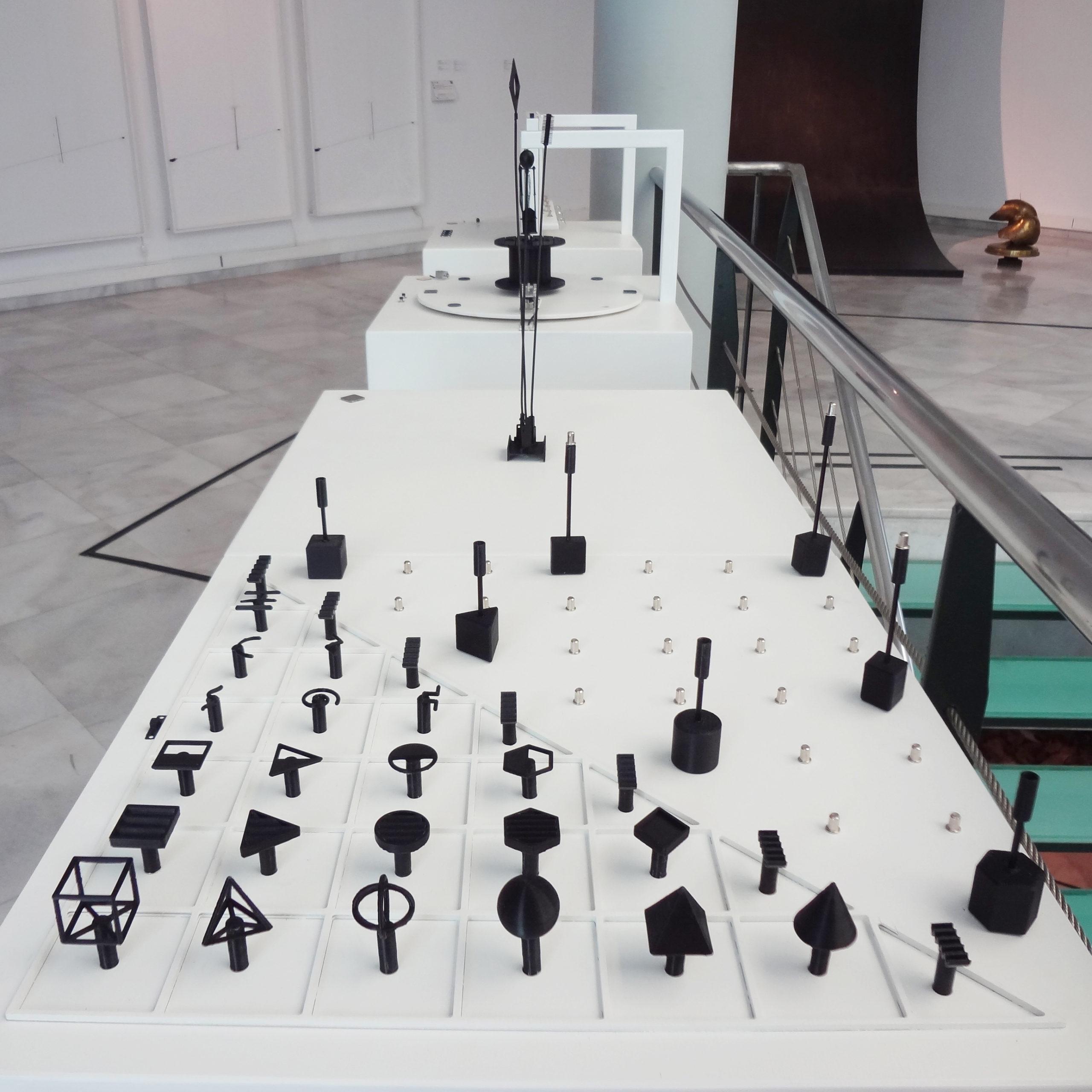 Όπτική από πάνω. Διαδραστικά Μουσειοπαιδαγωγικά Αντικείμενα για την ερμηνεία των έργων Σινιάλα, Μουσικό και Ηχητικό του καλλιτέχνη Τάκις, της συλλογής του MOMus-Μουσείου Σύγχρονης Τέχνης. Τρια λευκά ξύλινα κουτιά, φέρουν στην άνω πλευρά τους απτικά βοηθήματα που απτικοποιούν τα πρωτότυπα έργα και έχουν δημιουργηθεί με χύτευση σε μέταλλο από καλούπια που αποτελούν προϊόν τρισδιάστατης εκτύπωσης.