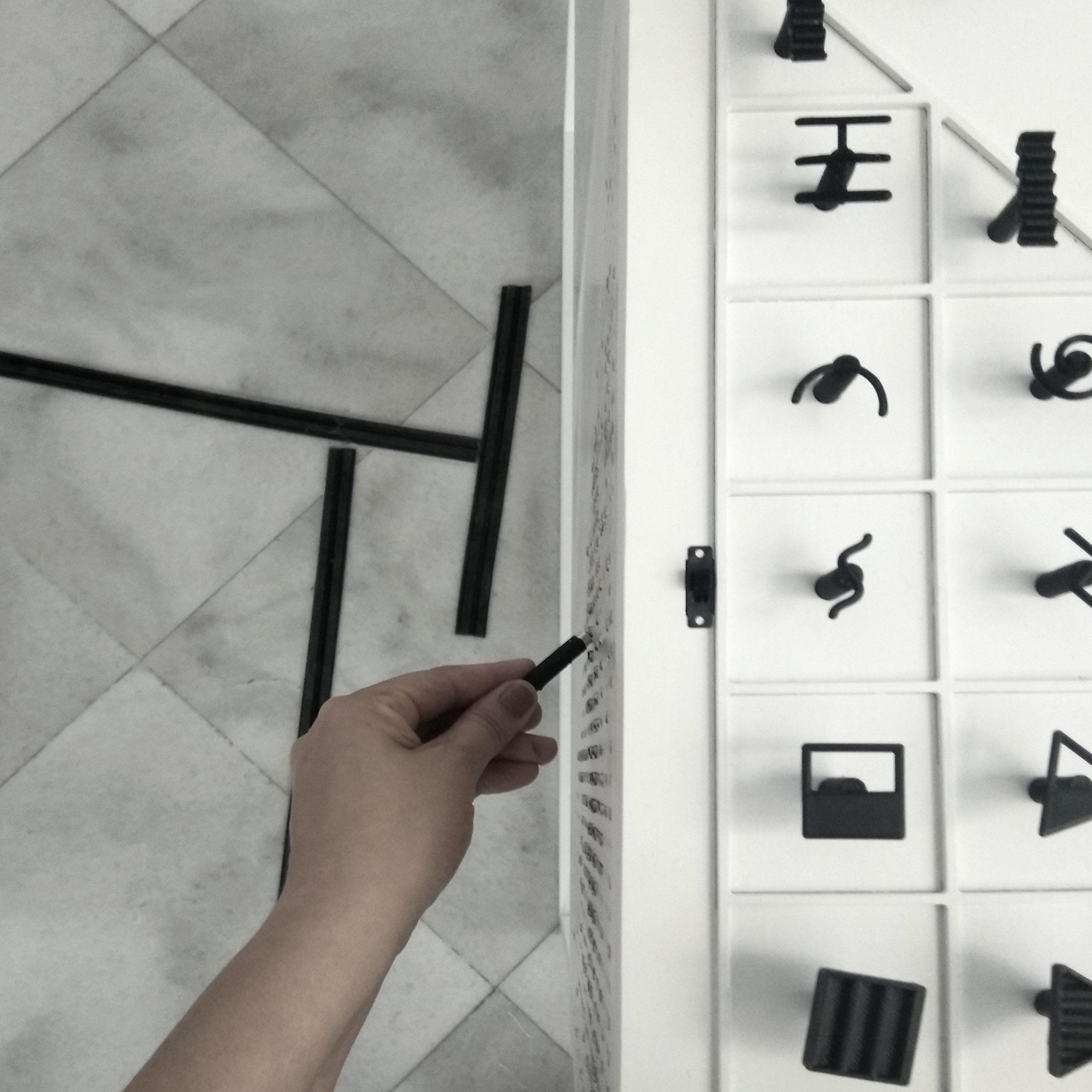 Διαδραστικά Μουσειοπαιδαγωγικά Αντικείμενα για την ερμηνεία του έργου Σινιάλα του καλλιτέχνη Τάκι, της συλλογής του MOMus-Μουσείου Σύγχρονης Τέχνης. Τα αντικείμενα έχουν τοποθετηθεί σε ένα ξύλινο λευκό κουτί και περιλαμβάνουν ένα αντίγραφο του έργου τέχνης σε μικρότερη κλίμακα, έναμαγνητικό πίνακα αλληλεπίδρασης και στοιχεία που παρουσιάζουν τα βασικά γεωμετρικά σχήματα, είδη γραμμών και μια ηχητική ερμηνεία των βασικών χρωμάτων. Στην εικόνα εμφανίζεται ο μαγνητικός πίνακας που με ένα μαγνητικό μολύβι ο χρήστης μπορεί να σχεδιάσει έλκοντας μαγνητικά τις μεταλλικές ψηφίδες πάνω στον τριγωνικό πίνακα αλληλεπίδρασης που βρίσκεται στην μπροστινή και δεξιά πλαϊνή όψη του κουτιού.