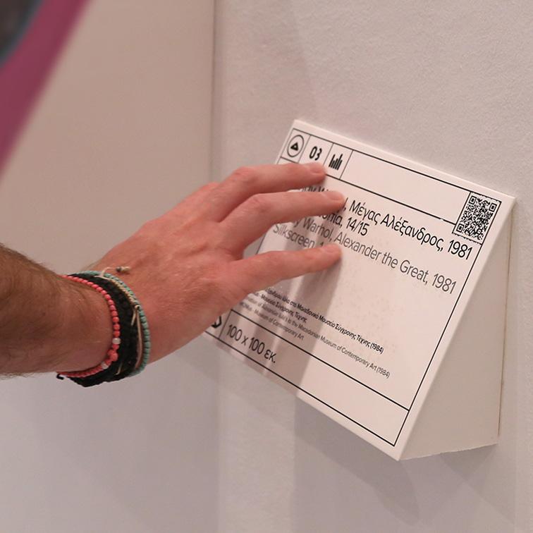 Λεζάντα έργου τέχνης με πληροφορίες σε ελληνική και αγγλική γλώσσα και μεταγραφή σε ελληνική braille, αποδοσμένη με ανάγλυφη διάφανη εκτύπωση και δυνατότητα ακουστικής περιγραφή με QR κωδικό
