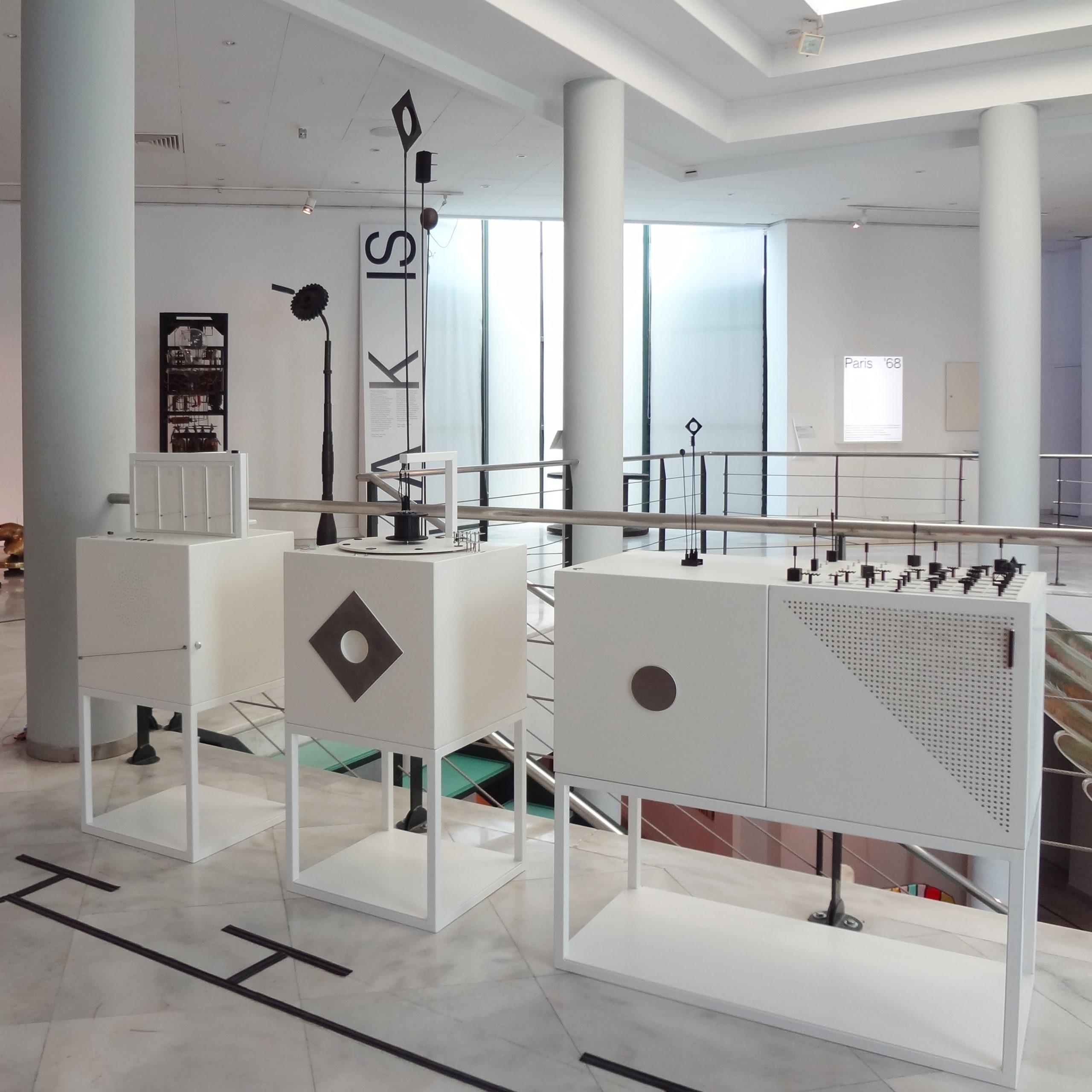 Διαδραστικά Μουσειοπαιδαγωγικά Αντικείμενα για την ερμηνεία των έργων Σινιάλα, Μουσικό και Ηχητικό του καλλιτέχνη Τάκις, της συλλογής του MOMus-Μουσείου Σύγχρονης Τέχνης. Τρια λευκά ξύλινα κουτιά, φέρουν στην άνω πλευρά τους απτικά βοηθήματα που απτικοποιούν τα πρωτότυπα έργα και έχουν δημιουργηθεί με χύτευση σε μέταλλο από καλούπια που αποτελούν προϊόν τρισδιάστατης εκτύπωσης. Το κάθε κουτί στην μπροστινή του πλευρά φέρει ένα στοιχείο από το κάθε έργο σε κλίμακα 1:1 και διαφορετικά στοιχεία με τα οποία ο επισκέπτης καλείται να αλληλεπιδράσει για να ανακαλύψει τα χαρακτηριστικά του έργου ή να δημιουργήσει από μόνος του συνθέσεις. Όλα τα βοηθήματα περιλαμβάνουν μαγνητικά και γεωμετρικά στοιχεία αποκαλύπτοντας τις έρευνες του καλλιτέχνη.