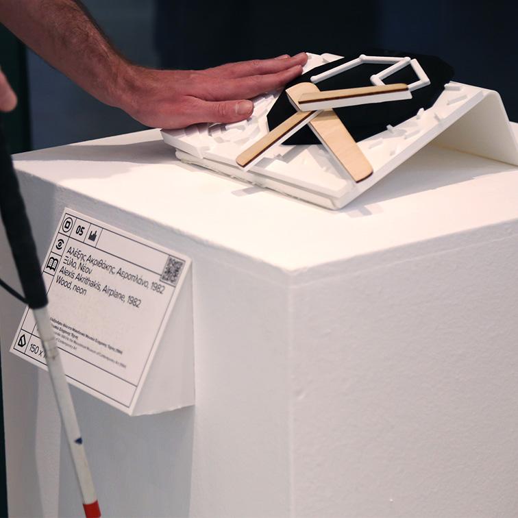"""Λεζάντα έργου τέχνης με πληροφορίες σε ελληνική και αγγλική γλώσσα και μεταγραφή σε ελληνική braille, αποδοσμένη με ανάγλυφη διάφανη εκτύπωση και δυνατότητα ακουστικής περιγραφή με QR κωδικό. Στην εικόνα πέρα από τη λεζάντα του έργου τέχνης εμφανίζεται και το απτικό βοήθημα του έργου """"Αεροπλάνο"""" που έχει δημιουργηθεί για την προσέγγιση του έργου του Αλέξη Ακριθάκη της συλλογής του ΜΟΜus-Μουσείου Σύγχρονης Τέχνης"""