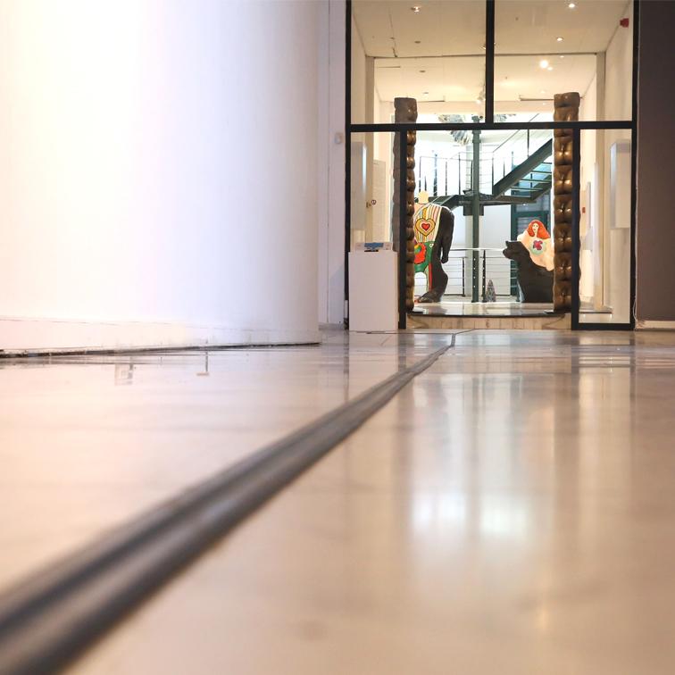 Φωτογραφία που παρουσιάζει την εφαρμογή του οδηγού όδευσης στο πάτωμα του μουσείου MOMus - Μουσείο Σύγχρονης Τέχνης. Όψη από χαμηλά, παρουσιάζεται ο διάδρομος που οδηγεί στο χώρο της εφαρμογής του προγράμματος MindsEye. Στο βάθος αριστερά διακρίνεται σε μικρό μέγεθος ο απτικός χάρτης της εισόδου στην αίθουσα Ιόλα, η γυάλινη πόρτα της εισόδου και τα γλυπτά Αδάμ και Ευα της Νικη ντε Σαντ Φαλ που υποδέχονται τον επισκέπτη στην αίθουσα του μουσείου.