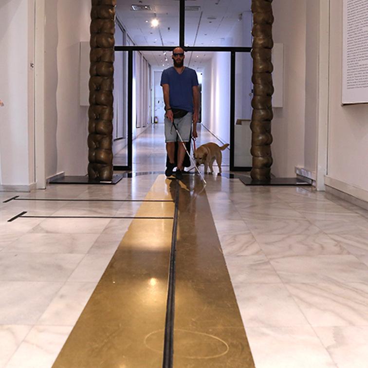 Φωτογραφία που παρουσιάζει την εφαρμογή του οδηγού όδευσης στο πάτωμα του μουσείου MOMus - Μουσείο Σύγχρονης Τέχνης. Εμφανίζεται ο Θανάσης Σιδέρης, με τη Φρίντα το σκύλο οδηγό να εισέρχεται στην αίθουσα Αλέξανδρου Ιόλα με το λευκό μπαστούνι στο χέρι. Ο οδηγός όδευσης είναι στη μέση της φωτογραφίας και έχει τοποθετηθεί πάνω σε μια χρυσή λωρίδα που βρίσκεται πάνω στο πάτωμα. Δεξιά και αριστερά από το Θανάση διακρίνονται οι στήλες του έργου του Νοβέλο Φινότι.
