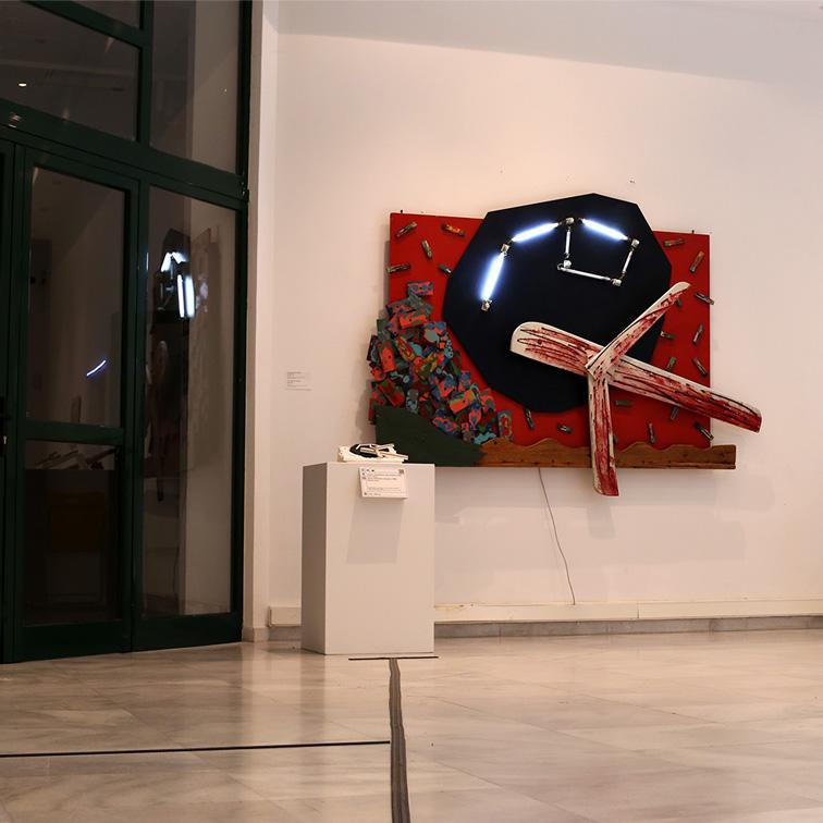 Φωτογραφία που παρουσιάσει την εφαρμογή του οδηγού όδευσης στο χώρο του MOMus Μουσείο Σύγχρονης Τέχνης. Η εικόνα παρουσιάζει τον οδηγό όδευσης που οδηγεί στην ευθεία στο απτικό βοήθημα του έργου του Αλέξη Ακριθάκη Αεροπλάνο που βρίσκεται κρεμασμένο στον τοίχο ακριβώς από πάνω και η διακλάδωση του οδηγού προς τα αριστερά που οδηγεί στο ασανσερ.