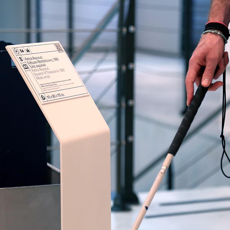 Λεζάντα έργου τέχνης με πληροφορίες σε ελληνική και αγγλική γλώσσα και μεταγραφή σε ελληνική braille, αποδοσμένη με ανάγλυφη διάφανη εκτύπωση και δυνατότητα ακουστικής περιγραφή με QR κωδικό. Μπροστά από τη λεζάντα του έργου που είναι τοποθετημένη σε κεκλιμένο μεταλλικό σταντ βλέπουμε το χέρι ενός ατόμου που κρατάει λευκό μπαστούνι
