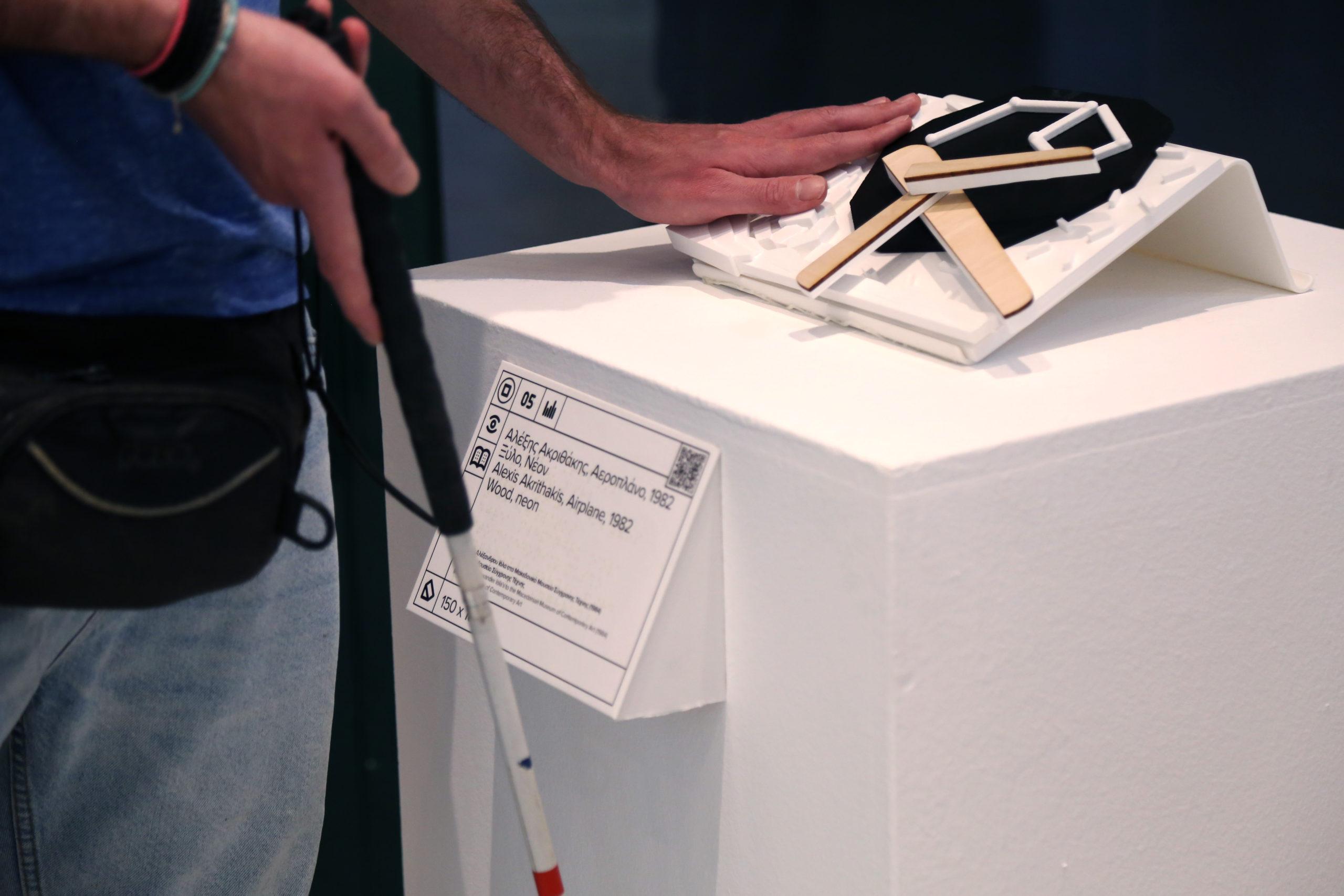 Εικόνα στιγμιότυπο από το βίντεο Ψηλαφώντας την Τέχνη στο Momus-Μουσείο Σύγχρονης Τέχνης 2019/20. Το στιγμιότυπο παρουσιάζει το απτικό βοήθημα που έχει δημιουργηθεί για το έργο του Αλέξη Ακριθάκη Αεροπλάνο με την τεχνολογία της τρισδιάστατης εκτύπωσης κατά την απτική διερεύνηση από χρήστη με οπτική αναπηρία. Ο χρήστης με το αριστερό χέρι ψηλαφεί το απτικό βοήθημα και με το δεξί κρατάει το λευκό μπαστούνι. Το απτικό βοήθημα είναι τοποθετημένο στην άνω πλευρά ενός βάθρου ενώ παράλληλα εμφανίζεται και η λεζάντα του έργου που είναι τοποθετημένη στη μπροστινή πλευρά του βάθρου κάτω από το απτικό βοήθημα και φέρει κείμενο σε μεγαλογράμματη γραφή, μεταγραφή σε ελληνική μπράιγ και ανάγλυφο QR κωδικό για πρόσβαση στην ακουστική περιγραφή του έργου τέχνης.