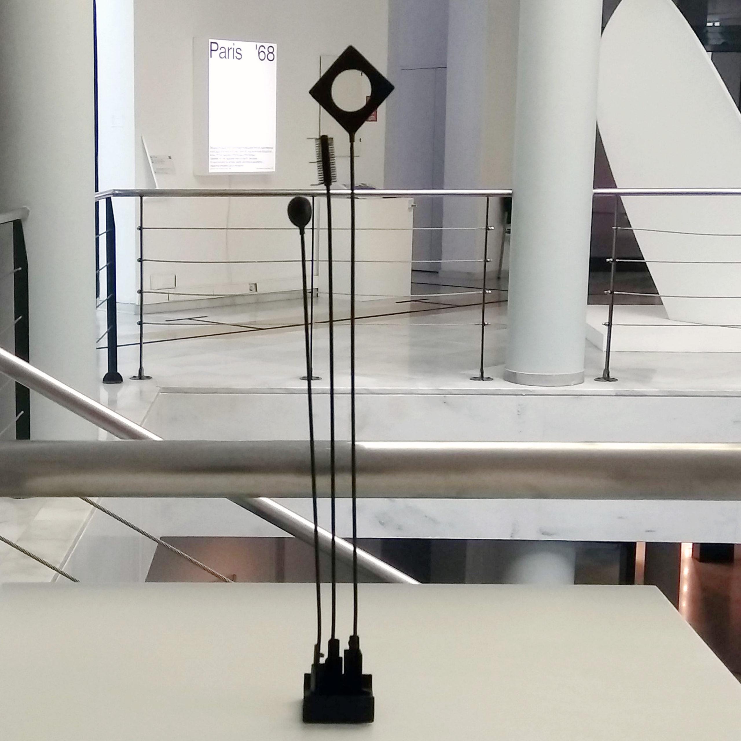 Απτικό βοήθημα για το έργο Σινιάλα. Έχει δημιουργηθεί με χύτευση σε μεταλλο σε καλούπι από τρισδιάστατη εκτύπωση. Είναι από μέταλλο σε χρώμα μαύρο. Αποτελείται από τρεις λεπτές βέργες που απολήγουν σε ένα γεωμετρικό στοιχείο, ένα ρόμβο με κενό στη μέση, μια σφαίρα και ένα κυλινδρικό σχήμα.