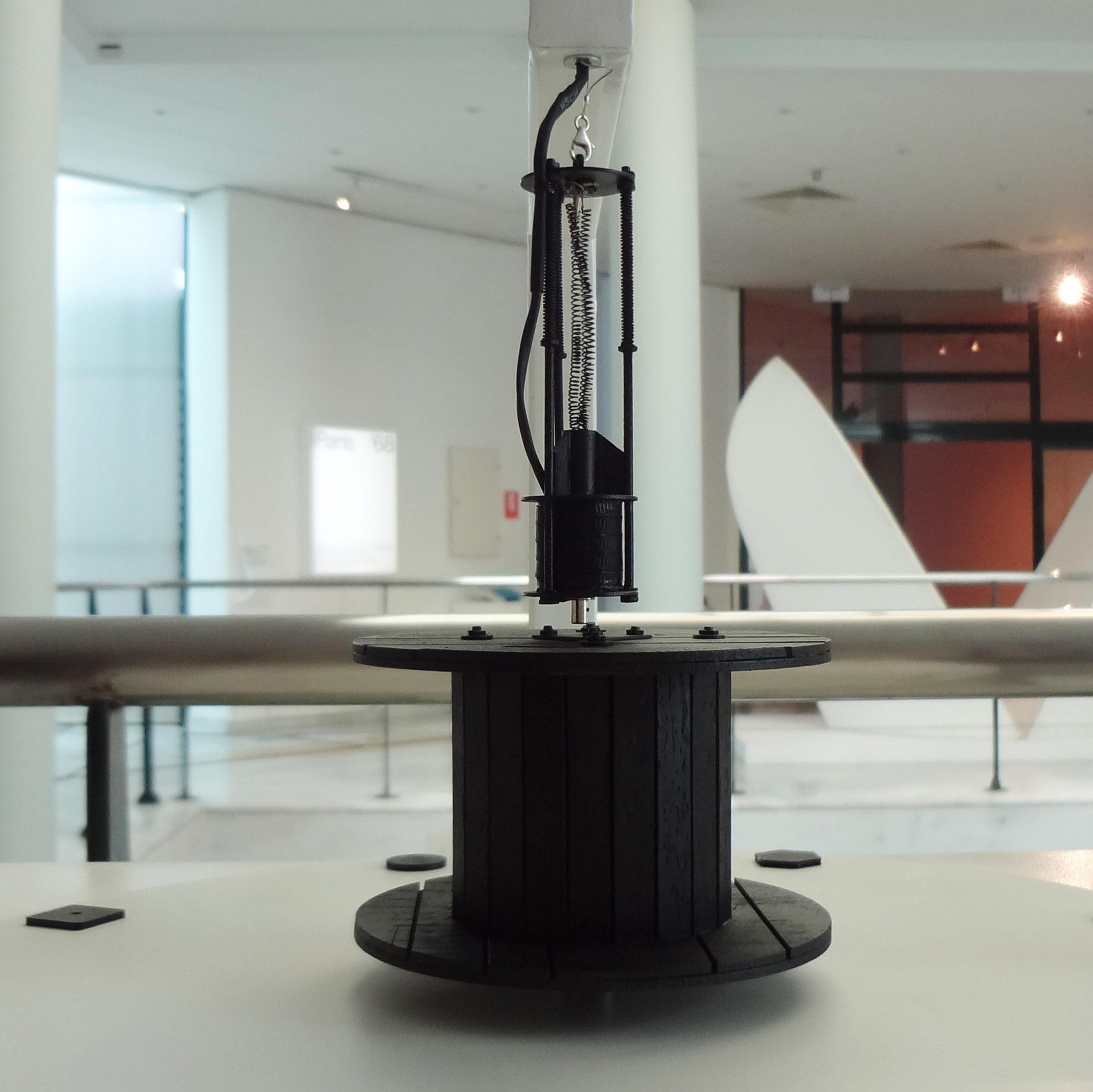 Λεπτομέρεια του απτικού βοηθήματος του έργου Ηχητικό. Παρουσιάζονται τα μέρη του έργου, το ξύλινο, μαύρο καρούλι και ο ηλεκτρομαγνήτης που κρέμεται πάνω από την επιφάνειά του σε κλίμακα 1:10 σε σχέση με το πρωτότυπο έργο.