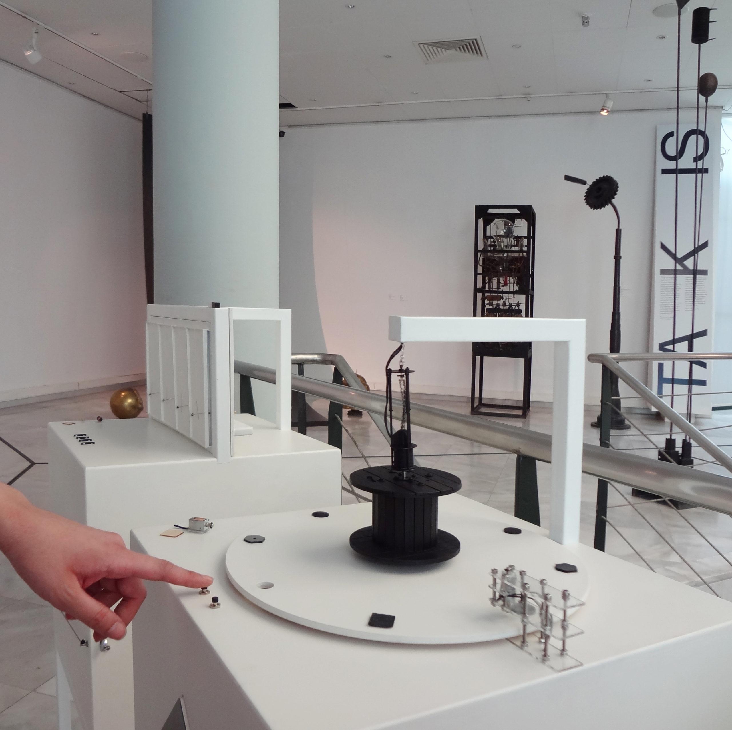 Στην εικόνα εμφανίζεται ένα χέρι που αγγίζει ένα διακόπτη που ενεργοποιεί τον ηλεκτρομαγνήτη του απτικού βοηθήματος του έργου τέχνης. Στην εικόνα επίσης διακρίνονται τα στοιχεία της άνω πλευράς του κουτιού, δηλαδή ο περιστρεφόμενος δίσκος με τα υλικά, το απτικό βοήθημα στο κέντρο του και ένας ηλεκτρομαγνήτης στη δεξιά πλευρά του δίσκου. Στο πίσω μέρος της εικόνας διακρίνονται άλλα έργα του καλλιτέχνη και μια μεγάλη επιγραφή με το όνομά του.