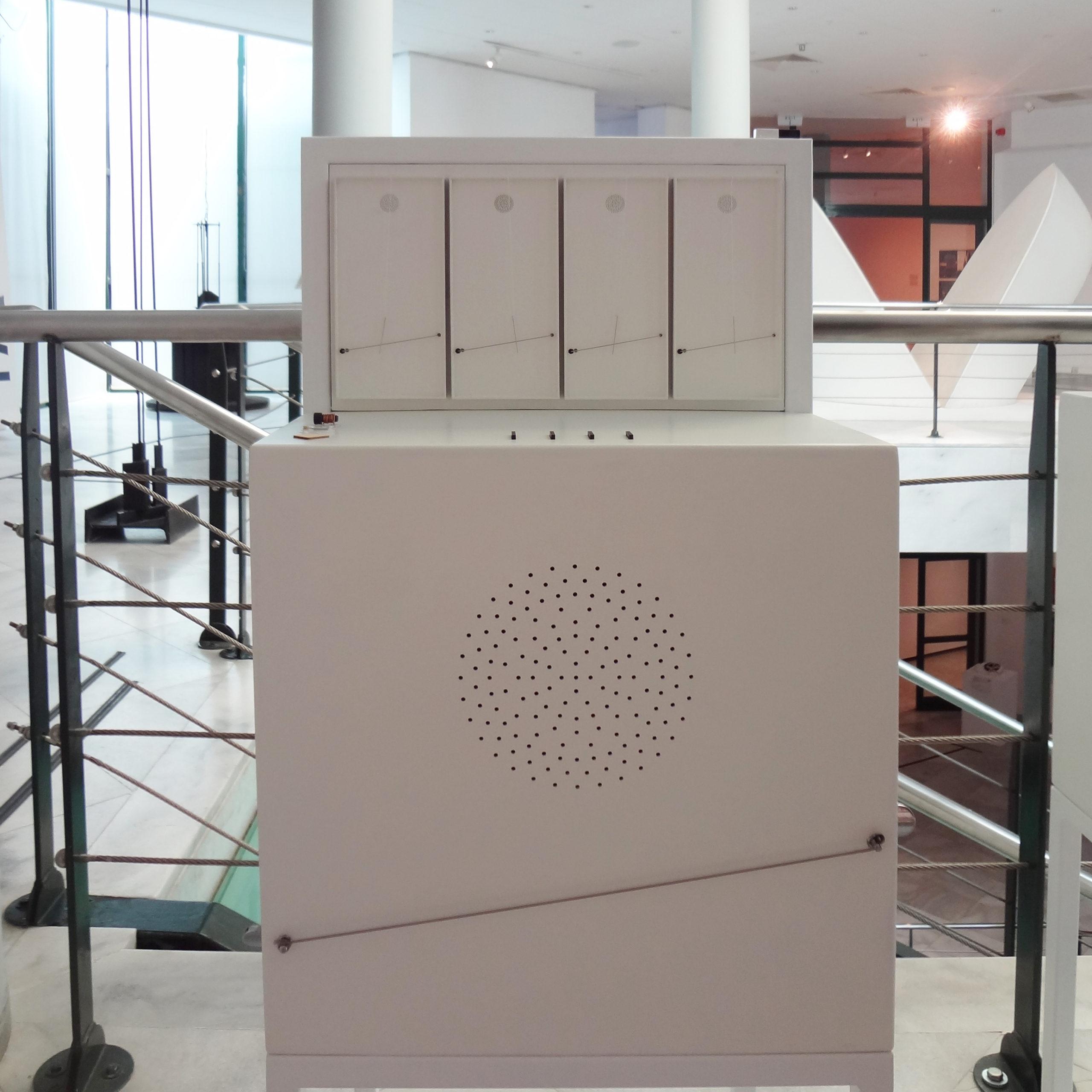Όψη από μπροστά. Λευκό ξύλινο κουτί με απτικό βοήθημα για το έργο μουσικό, που φέρει στοιχεία στην άνω και μπροστινή πλευρά . Στην άνω πλευρά του φέρει απτικό βοήθημα που περιλαμβάνει τέσσερις ορθογώνιες μουσικές κιθάρες σε κλίμακα 1:10. Η μπροστινή πλευρά εμφανίζει ένα ηχείο που αποτελείται από πολυάριθμες τρύπες, ακριβώς στην ίδια κλίμακα και μορφή με το ηχείο του πρωτότυπου έργου.