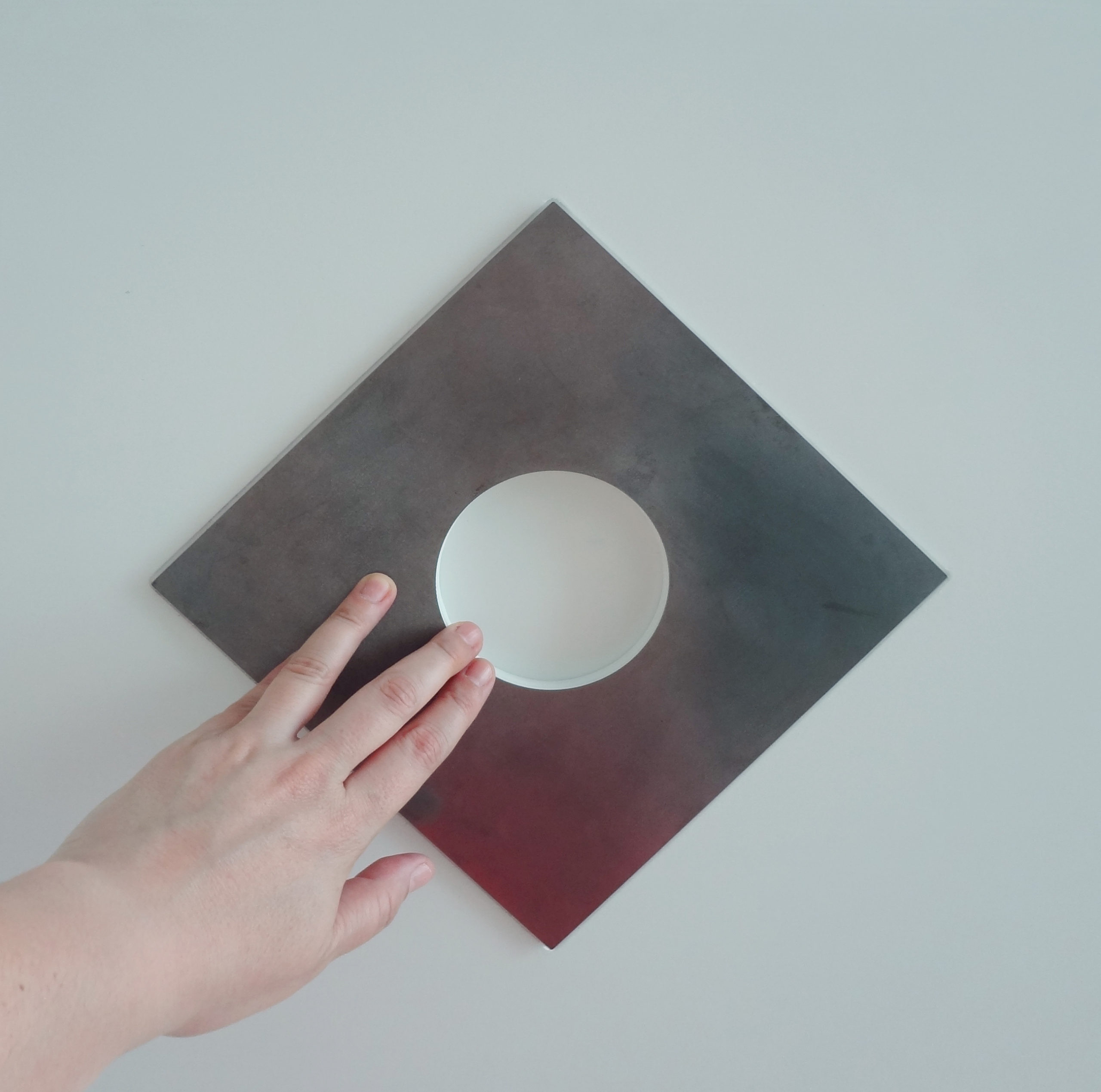 Λεπτομέρεια της μπροστινής όψης του κουτιού. Παρουσιάζεται ένας μεταλλικός ρόμβος που έχει ένα κυκλικό κενό στο κέντρο του και ένα χέρι που αγγίζει το μεταλλικό αυτό στοιχείο. Ο μεταλλικός ρόμβος είναι τοποθετημένος πάνω στο λευκό ξύλινο κουτί και αποτελεί αντίγραφο του στοιχείου που βρίσκεται στο κέντρο της άνω πλευράς του καρουλιού σε κλίμακα 1:1 σε σχέση με το πρωτότυπο έργο.