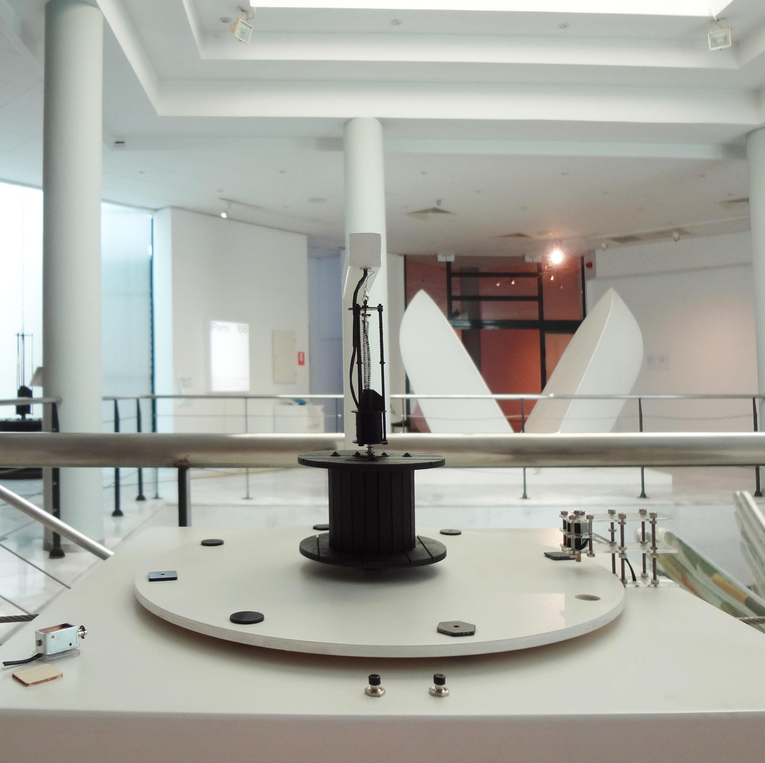 Στην εικόνα εμφανίζεται η άνω επιφάνεια του δεύτερου διαδραστικού κουτιού για την προσέγγιση του έργου Ηχητικό του καλλιτέχνη Τάκις. Στο κέντρο του περιστρεφόμενου ξύλινου δίσκου, βρίσκεται το απτικό βοήθημα του έργου. Αυτό περιλαμβάνει τη μικρογραφία ενός μαύρου, ξύλινου καρουλιού σε κλίμακα 1:10 πάνω από το οποίο κρέμεται ένας μαύρος ηλεκτρομαγνήτης με ελατήρια.