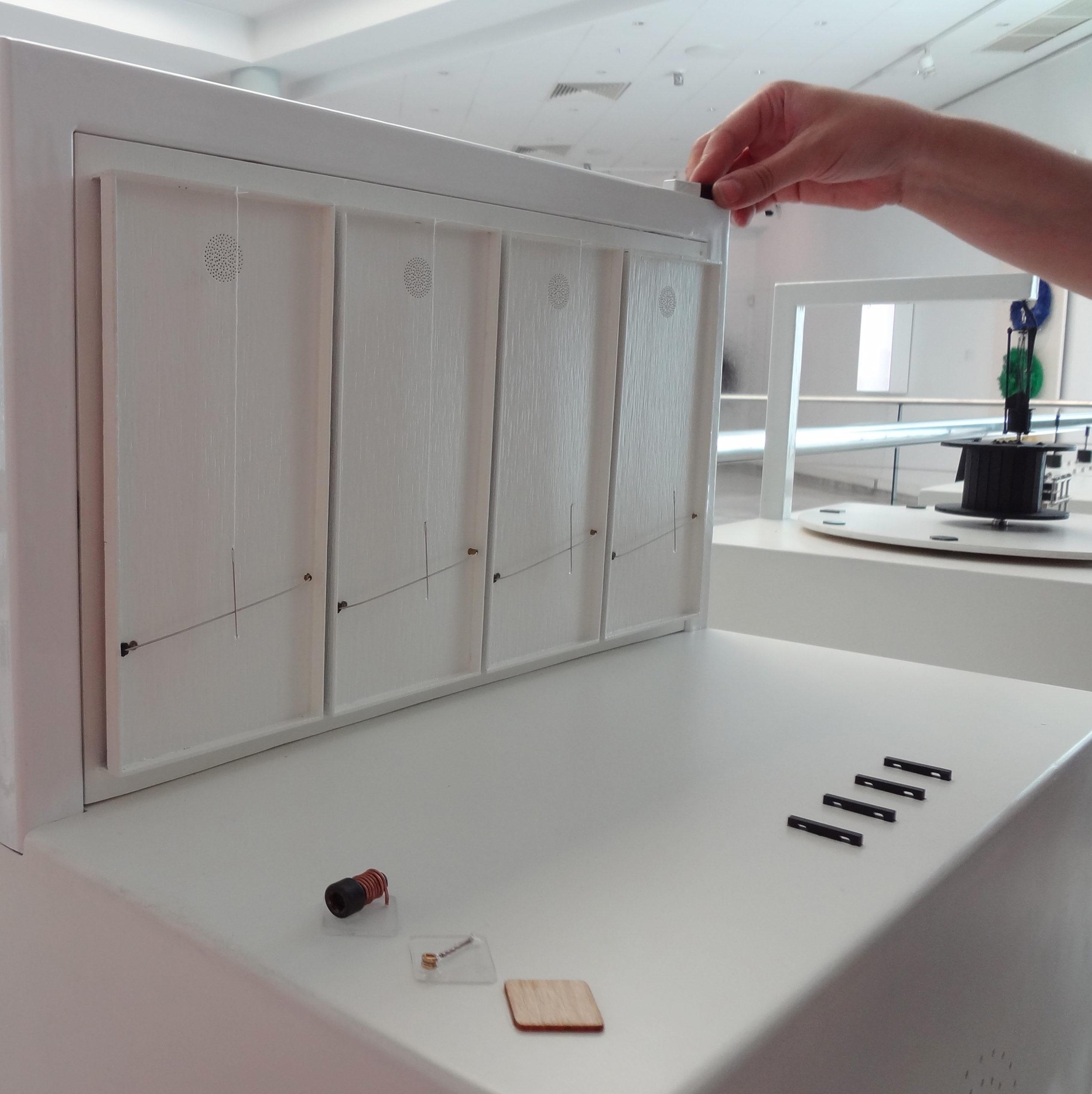 Λεπτομέρεια από το μουσειοπαιδαγωγικό κουτί που δείχνει το απτικό βοήθημα, και ένα χέρι που πιάνει το μαγνήτη που βρίσκεται τοποθετημένος στο μεταλλικό πλαίσιο που στηρίζει το απτικό βοήθημα. Με το μαγνήτη αυτό κάποιος ενεργοποιεί τους μαγνητικούς διακόπρες που θέτουν σε κίνηση τις βελόνες του έργου.